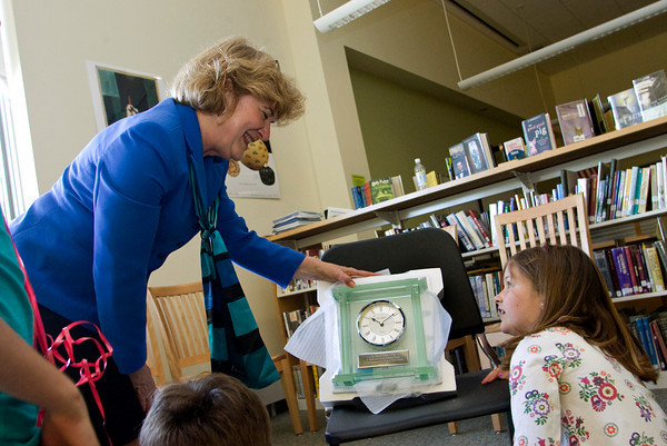 Manchester: Superintendent of the Manchester Essex school district Marcia O'Neil opens her gift, an inscribed clock, at her retirement party in the library of the Manchester Essex High School Monday afternoon. Pictured right is Sarah Murphy, 10. Mary Muckenhoupt/Gloucester Daily Times