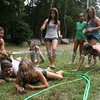 Gloucester: YMCA Camp Spindrift Councilor Jess Dunn holds a hose steady as Rikki Johnsen and Chloe Kenyon crawl under the water to keep cool yesterday afternoon. Fellow campers Marlaina Rallo, Lindsey Parrish. Rebecca Paul Molly White and Lacey Gibbs wait to take their turn. The camp runs until school starts at the end of August. Photo by Kate Glass/Gloucester Daily Times