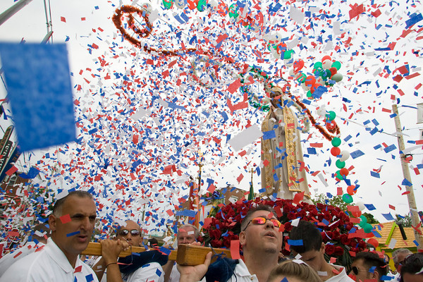 Gloucester: Statue holders including Mike Carter, center, look up at confestti is blown in the air at the end of the Fiesta procession Sunday. Mary Muckenhoupt/Gloucester Daily Times