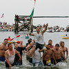 Gloucester: Peter Cannavo gets carried onto the beach after winning Saturday's greasy pole. Mary Muckenhoupt/Gloucester Daily Times