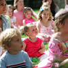 """Manchester: Madeleine Jones, 11 months, listens to librarian Sara Collins read """"Pinkalicious"""" at the Pinkalicious tea party for National Pink day at the Manchester Public Library Wednesday afternoon. Mary Muckenhoupt/Gloucester Daily Times"""