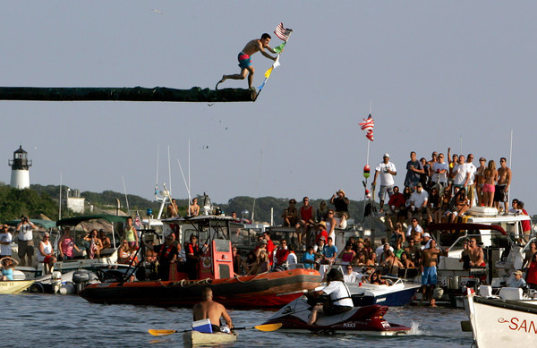 Gloucester: Joe Bracaleone is the first one to get to the flag during the greasy pole competition Friday night. Mary Muckenhoupt/Gloucester Daily Times