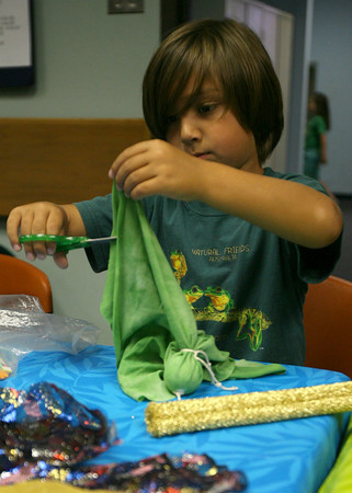 Gloucester: Isak Lam, 7, trims fabric as he creates a puppet at the Sawyer Free Library on Wednesday morning following the Rosalita's Puppets Show. Photo by Kate Glass/Gloucester Daily Times
