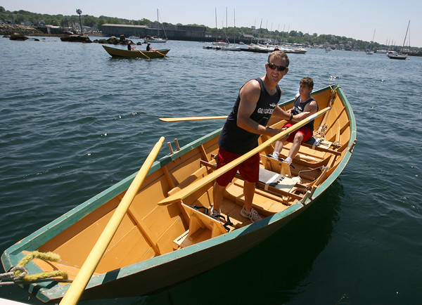 Gloucester: John Swift and Mick Cote hand their oars to the judges to be measured before the start of the Senior's Division of the International Dory Boat Races at the Jodrey State Fish Pier on Saturday. A rumor had circulated that their oars were an illegal length, but they were correct. Photo by Kate Glass/Gloucester Daily Times