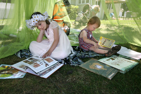Essex: Kaitlyn Borge, 5, and Sean Gauthier, 2, both of Gloucester, read in the shade during the 7th Annual Fairy Festival at Underwood Photography in Essex on Saturday. Photo by Kate Glass/Gloucester Daily Times