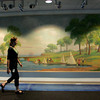 Gloucester: Nicole MacDonald, Cooperative Programs Specialist at NOAA, walks past a mural done by Gloucester's Oscar Anderson in the 1930s that NOAA paid to restore and now hangs in the lobby of the new NOAA building in Gloucester. Mary Muckenhoupt/Gloucester Daily Times
