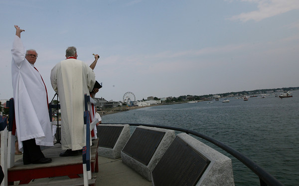 Gloucester: Father John Walsh, left, participates in the blessing of the fleet at the Fishermen's Memorial yesterday afternoon. Photo by Kate Glass/Gloucester Daily Times