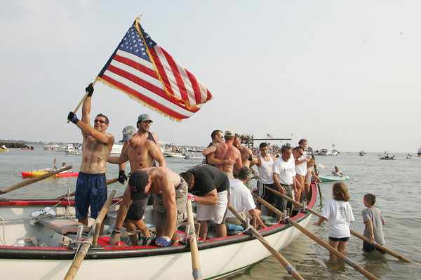 Gloucester; Joe Sanfilippo waves the American flag after KOAS is named mens senior seine boat chams Sunday at Pavilion Beach. Mary Muckenhoupt/Gloucester Daily Times