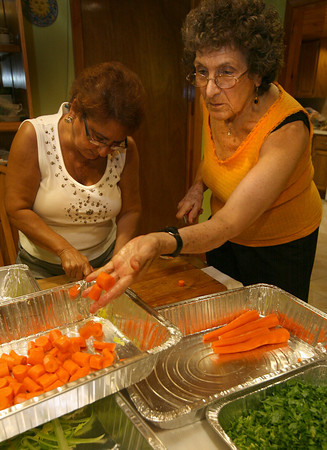 Gloucester: Grace Cottone, left, and Grace F. Favazza chop carrots and celery for the monkfish stew, which is one of three dishes the Fishermen's Wives Association made for the New Fish Festival at the Gloucester House last night. Photo by Kate Glass/Gloucester Daily Times