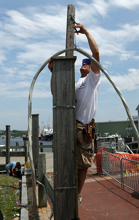Gloucester: John Novello takes down the electrical wiring from the altar at St. Peter's Square yesterday afternoon. Photo by Kate Glass/Gloucester Daily Times