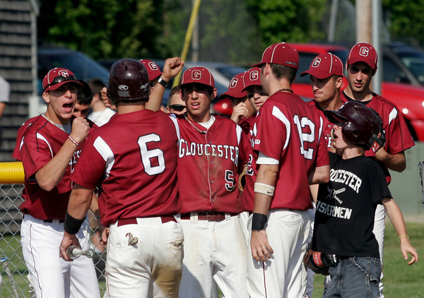Gloucester: Sal Taormina and Caulin Rogers greet Brett Cahill at home plate as he scores during their game against Wayland in the first round of the MIAA Division 2 North Baseball Tournament at Nate Ross Field yesterday afternoon. Photo by Kate Glass/Gloucester Daily Times