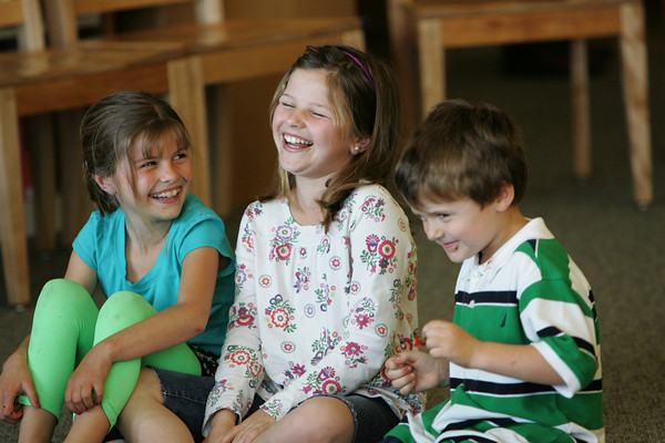 Manchester: From left, Colleen Murphy, 8, her sister Sarah, 10, and brother Michael, 6, begin to giggle during Superintendent Macia O'Neil's retirement party at Manchester Essex High School Monday afternoon.  The kids were attending the party with their father, Paul Murphy, the assistant principal at Manchester Essex High School. Mary Muckenhoupt/Gloucester Daily Times