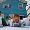 Gloucester: Sean Reardon, left, and Chris Cassettari, right, look over at Trevor Parisi as he tries to eat through his pie plate during the pie eating contest at Beach Court Saturday aftertoon. Mary Muckenhoupt/Gloucester Daily Times