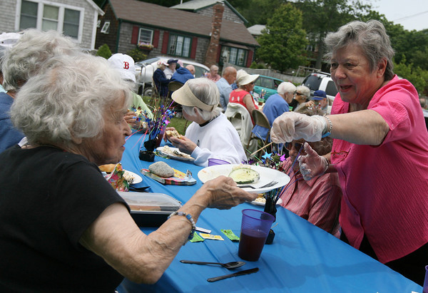 Rockport: Peg Shea places a cucumber slice on Kay Murphy's Plate during the Neighbors Caring for Neighbors Barbecue on the Legion grounds on Wednesday afternoon. The cookout was sponsored by Den Mar Rehabilitation and Nursing Center and the Rockport Council on Aging. Photo by Kate Glass/Gloucester Daily Times