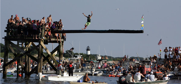 Gloucester: Peter Asaro competes in Friday night's greasy pole. Mary Muckenhoupt/Gloucester Daily Times