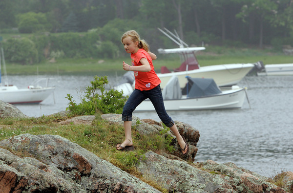 Manchester: Sophia Puchniak, 12, runs up the rocks at Tuck's Point while playing with her brother Matthew and friend Lila Leonard and making the best of a cool, foggy Wednesday afternoon. Mary Muckenhoupt/Gloucester Daily Times