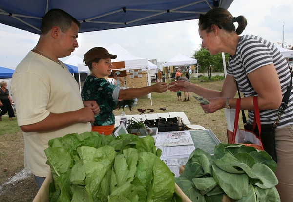 Gloucester: Claire Sanford, right, purchases greens from the Backyard Growers, Jacob Souza and Lara Lepionka, at the Cape Ann Farmer's Market on Rogers Street yesterday afternoon. Photo by Kate Glass/Gloucester Daily Times