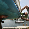 Rockport: Jack Ketchopulos paints the hull of his harpoon boat, Nora Sandy, at the Old Granite Pier on Wednesday afternoon. Ketchopulos has been busy lately, painting three of his boats, which he is hoping to sell. Photo by Kate Glass/Gloucester Daily Times