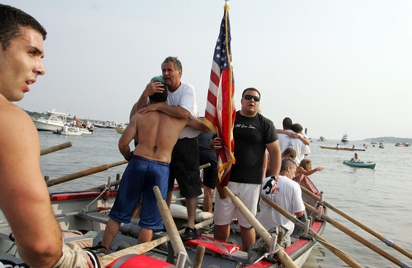 Gloucester: Kaos Coxswain Joe Novello hugs rower Joe Sanfilippo after Kaos wins the mens senior seine boat championship Sunday at Pavilion Beach. Pictured right holding the American flag is Mike Mitchell, and left is Tony Testaverde. Mary Muckenhoupt/Gloucester Daily Times