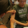 Mandy Roberge gives Marius Fauteux a henna tattoo at the Manchester Library. Fauteux is visting Manchester from Canada. Photo by Maria Uminski/Gloucester Daily Times