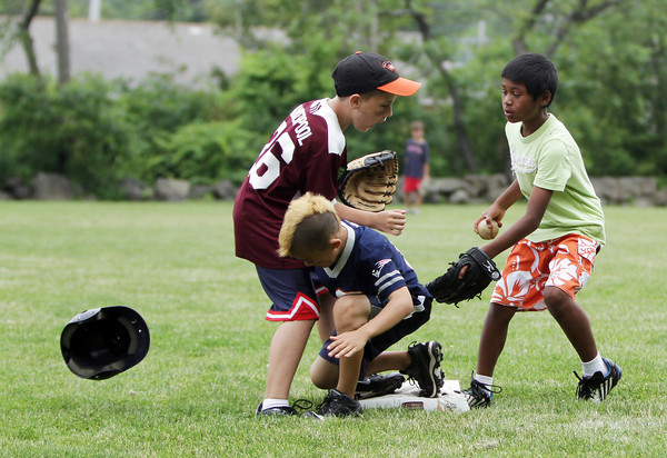 David Le/Gloucester Daily Times. Sam Mellen, 9, of Rockport, center, kneels safely on second base after crashing into Dillon Vanderpool, also 9 of Rockport, after losing his helmet while Jayce Rowen, 10 of Rockport arrives late to apply the tag. 6/28/11.