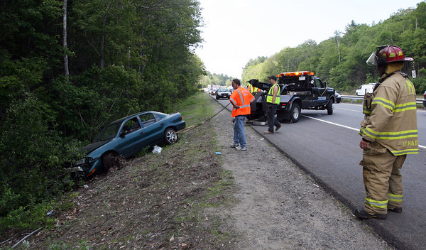 Manchester Fire Lt. Clinton Hatch looks on as Cross Towing removes a vehicle from the woods on Route 128 south near the School Street exit. Photo by Kate Glass/Gloucester Daily Times