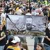 Boston: Eric Ryals and Chris Fortunato of Chelmsford, Mass hold up a 4x6 foot poster featuring Goalie Tim Thomas as Spartaus at  the Bruins Victory parade held Saturday in Boston. Desi Smith/Gloucester Daily Times. June 18,2011.