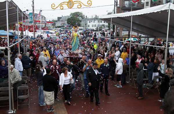 David Le/Gloucester Times. The Statue of St. Peter is showered in confetti as it is brought into St. Peter's Square following a short procession from St. Peters Club to kick off Fiesta 2011. 6/24/11.