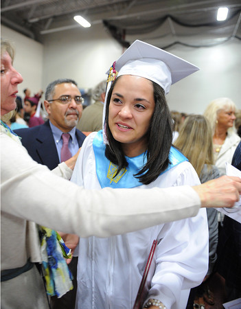 Gloucester: Ellida Cornavaca looks to her classmates as she gets a big hug from her mother Janice Reiloi as her father Reberto looks on,at the end of Graduation Sunday afternoon at the Benjamin A. Smith Fieldhouse.   Desi Smith/Gloucester Daily Times. June 12,2011