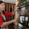 David Le/Gloucester Daily Times. Kathleen Erickson, co-owner of Savour Wine and Cheese on Washington St. in downtown Gloucester, demonstrates how to pour a sample of wine that will be complimentary for any customer, from a special wine machine that keeps various wines at different temperatures and will keep wine fresh up to 60 days. 6/28/11.