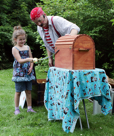 "David Le/Gloucester Daily Times.  Awesome"" Robb Preskins, also known as Captain Robbie Bones, right, asks for the help of Lilly Morrell, 6, of Rockport to make a rabbit appear from his magical box, during the Sky Pirate Show at Millbrook Meadow Park in Rockport on Wednesday afternoon. 6/29/11."