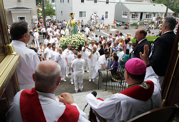 David Le/Gloucester Times. Father Ronald Garabaldi, left, sits with Bishop Peter Ugiletto, as he waves to the crowd and to the statue of St. Peter as it arrives in front of St. Ann's Church on Sunday afternoon. 6/25/11.