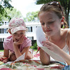 David Le/Gloucester Daily Times. Lilly Coote, 7, of Manchester, left, and Madeline Lai, 8, also of Manchester, relax while writing poems on picnic blankets outside Manchester Public Library on Monday morning as part of a Poetry n' Picnic event held by Sara Collins and Barbara Flaherty. 6/27/11.
