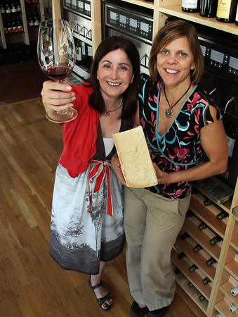"David Le/Gloucester Daily Times. Kathleen Erickson, left, one of the owners of Savour Wine and Cheese, and Krista Julian the ""Cheese Whiz"" prepare to open the doors to Savour on Thursday. 6/28/11."
