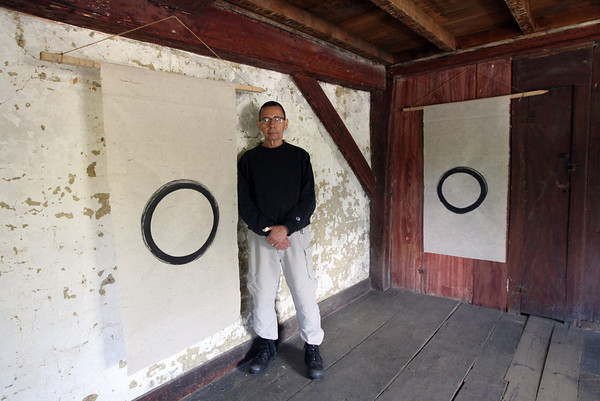"Gloucester: Jay Lee Jaroslav stands with two of his sacred circle ""Enso"" images, 100 of which will be on display at the White-Ellery House today. The display will be open from 11-3. Photo by Kate Glass/Gloucester Daily Times"