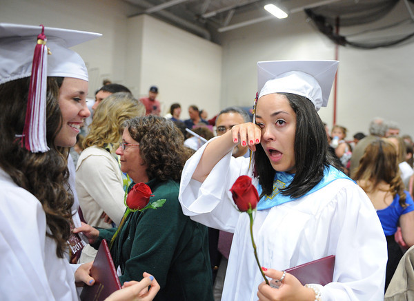Gloucester: Ellida Cornavaca wipes way some happy tears with a classmate at the end of Graduation Sunday afternoon at the Benjamin A. Smith Fieldhouse.   Desi Smith/Gloucester Daily Times. June 12,2011