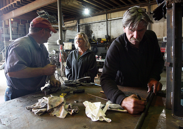 Viking Gustafson, manager of the Gloucester Marine Railways on Rocky Neck, chats with Doug Parsons and Preston Carter as they make parts for the Beaver, which is being restored for the Boston Tea Party Museum. Photo by Kate Glass/Gloucester Daily Times