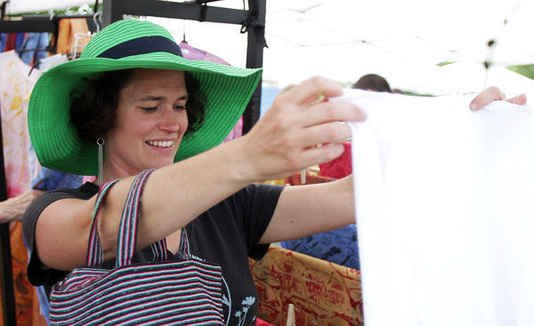 David Le/Gloucester Daily Times. Heidi Wakeman, of Gloucester examines a handmade cloth at the opening of the Cape Ann Farmer's Market at Stage Fort Park in Gloucester on Thursday afternoon. 6/30/11.