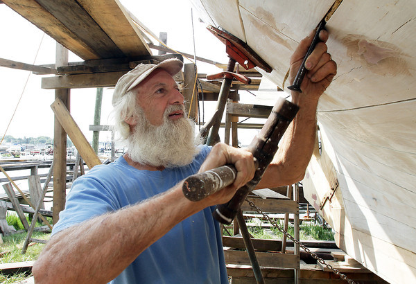 David Le/Gloucester Daily Times. Steve Willard, of Marblehead, works to hammer cotton caulking into the spaces in between planks on the side of the Schooner Ardelle in Burnham's Boat Yard on Wednesday morning in preparation for the launch on July 9th. 6/29/11.