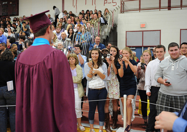 Gloucester: Connor Olson stops to have his picture taken by friends and family, Sunday afternoon at Graduation held inside at the Benjamin A. Smith Fieldhouse.   Desi Smith/Gloucester Daily Times. June 12,2011