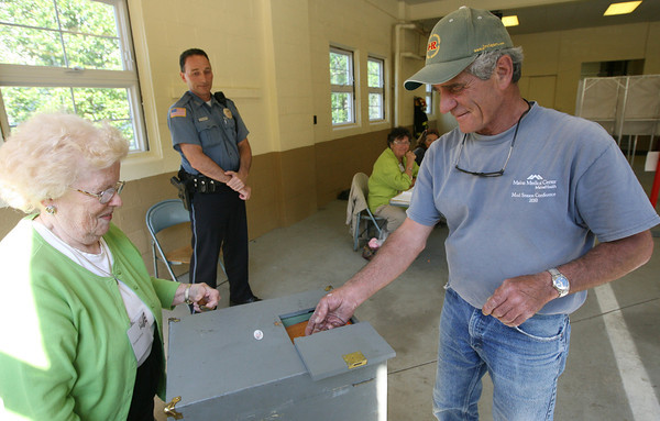 Ron Gauthier casts his ballot in the special override election in Essex as Genevieve Guerin turns the crank on the ballot box. Looking on is Essex Police Officer Rob Gilardi. Photo by Kate Glass/Gloucester Daily Times