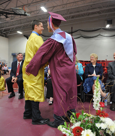 Gloucester: Out going Class Vice President Geoffrey gives Jr Sean Kennedy a tap on the butt during the Transfer of Leadership Sunday afternoon at Graduation held inside at the Benjamin A. Smith Fieldhouse.   Desi Smith/Gloucester Daily Times. June 12,2011
