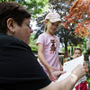 David Le/Gloucester Daily Times. Featured Manchester poet Barbara Flaherty, left, hands a piece of paper to Lilly Coote, 7 of Manchester, while Madeline Lai, 8, also of Manchester looks on. 6/27/11.