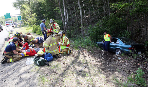 Manchester Firefighters treat two people who were injured after their car struck another vehicle and went off the road on Route 128 south just before the School Street exit yesterday afternoon. Photo by Kate Glass/Gloucester Daily Times