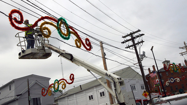 Dave Souza hangs the decorations for Fiesta around St. Peter's Square yesterday afternoon. The first Novena was held last night and the formal opening will be held next Friday. Photo by Kate Glass/Gloucester Daily Times