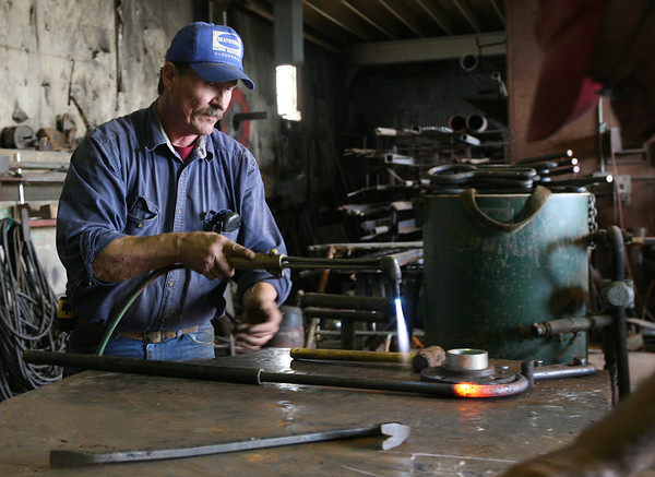Edward Wayman shapes parts for the Beaver, one of the ships being restored at Gloucester Marine Railways for the Boston Tea Party Museum. Photo by Kate Glass/Gloucester Daily Times