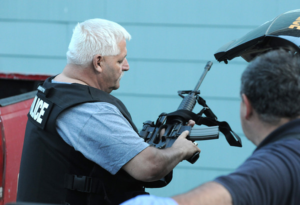 Gloucester: Lt Joe Aeillo checks his weapon, as Patrolman Mark foote looks on during the 3 hour standoff on Ashland Place Thursday night. Desi Smith/Gloucester Daily Times.