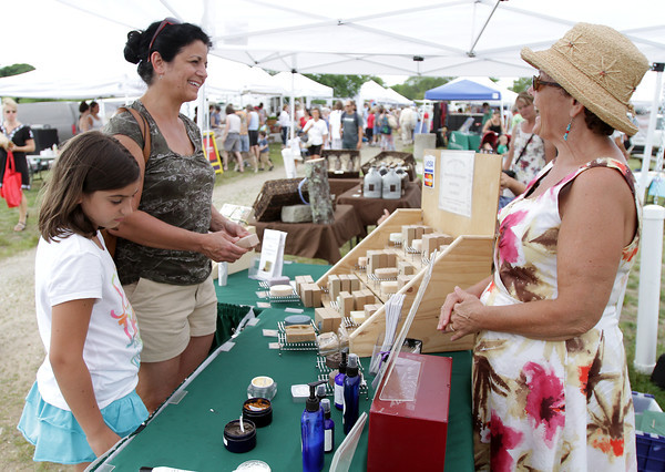 David Le/Gloucester Daily Times. Lynne Frick, center, and Deb Scanlon, owner of Grace Farm Organics, right, share a laugh while, Emily Frick, 9, of Gloucester, checks out some of the items for sale at the opening of the Cape Ann Farmer's Market at Stage Fort Park in Gloucester on Thursday afternoon. 6/30/11.