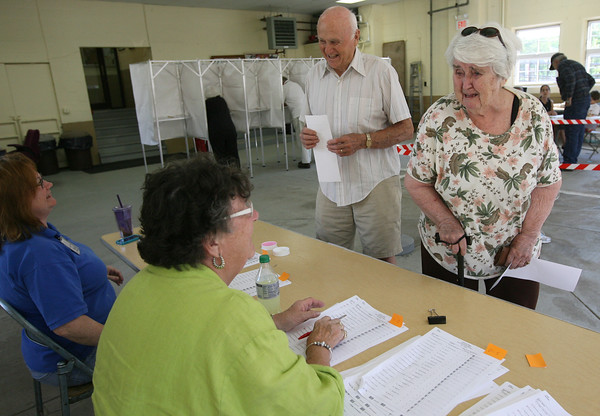 David and May Mears joke with election volunteers as they cast their ballot in the special Essex override election yesterday. Photo by Kate Glass/Gloucester Daily Times