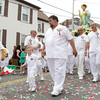 David Le/Gloucester Times. Jack Nicastro waves an Italian flag as he and Dominic Nicastro lead the statue of St. Peter down Prospect St. on Sunday afternoon. 6/25/11.